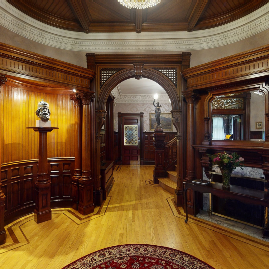 Interior snapshot of the Embassy of Hungary from a 3D Virtual Tour. Photo features a rounded archway made of dark wood with light brown flooring beneath.